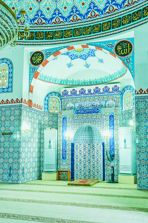 ALANYA, TURKEY - MAY 8, 2017: The mihrab of Hasan Senli Saray mosque decorated with glazed tiles with islamic patterns, the calligraphic plates, painted patterns and Arabic inscriptions surround the niche, on May 8 in Turkey. Editorial