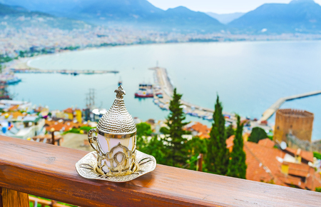 The Ottoman coffee cup, decorated with inlay patterns with the old marina of Alanya on background, Turkey.