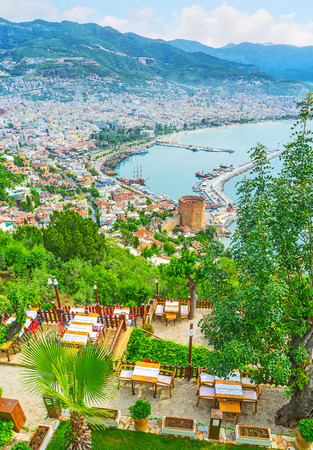 The cozy restaurants on the Castle hill are hidden in shade of local gardens and opens picturesque views on the old town of Alanya, Turkey.