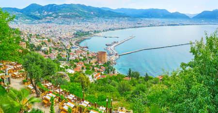 The architecture of old Alanya in frame of greenery, growing on the slopes of Castle hill, Turkey.