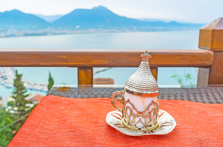 Authentic Ottoman coffee cup on the table of outdoor restaurant on the Castle Hill slope with the Taurus mountains behind the harbor, Alanya, Turkey.