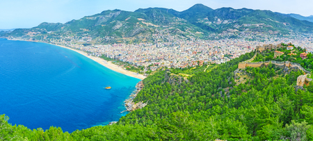 The slope of Alanya peninsula is covered with coniferous forest and neighboring with Kleopatra beach, that is seen from the Castle hills top, Turkey.