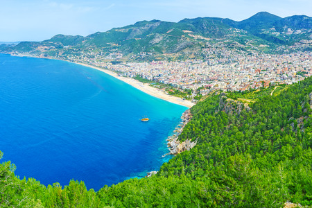 city park boat house: The beachline of Alanya is separated with the rocky peninsula, famous among the tourists for preserved Castle, lush coniferous forests and old towns neighborhood, Turkey. Stock Photo
