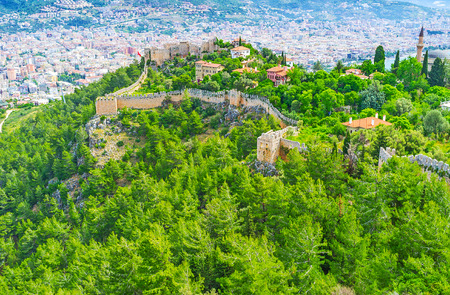 seljuk: The winding fortress wall runs along the Castle hill, covered with green coniferous forest, the modern districts of resort are seen on background, Alanya, Turkey. Stock Photo