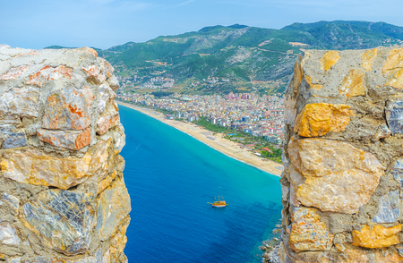 seljuk: The view on Kleopatra beach, modern city and green Cilician mountains through the hole between the old battlements of Alanya castle, Turkey. Stock Photo