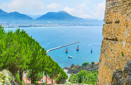 The seascape of Alanya with the medieval ramparts of the fortress, tourist ships at the coast and lush pines, growing on Castle hill, Turkey. Stock Photo