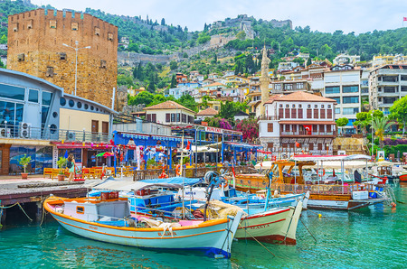 ALANYA, TURKEY - MAY 9, 2017: The boats of local fishermen moored next to the most popular fishing taverns in old port next to the Red Tower, on May 9 in Alanya.