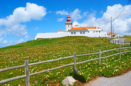 The westernmost lighthouse of the European mainland located on the high cliff of Cape Roca and surrounded by green meadow of blooming hottentot-fig succulent, Sintra, Portugal.