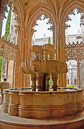BATALHA, PORTUGAL - APRIL 30, 2012: The Lavabo fountain in Royal Cloister of King John I in Convent of St Mary of Victory surrounded by carved arches, on April 30 in Batalha.