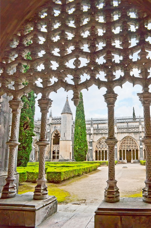 BATALHA, PORTUGAL - APRIL 30, 2012: The view on the Cloister of King John I in Convent of Santa Maria da Vitoria through the complex stone decors of the entrance portal, on April 30 in Batalha.