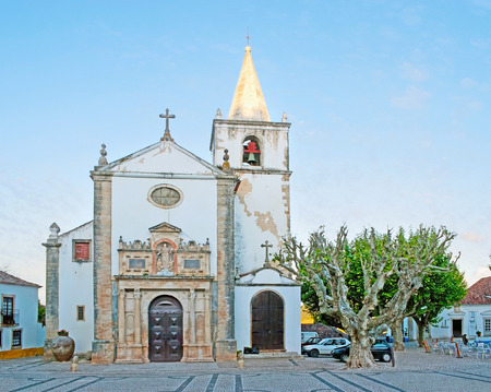 OBIDOS, PORTUGAL - APRIL 30, 2012: The St Mary Square is the center of the town, here locates medieval St Mary Church with carved stone portal, on April 30 in Obidos. Editorial