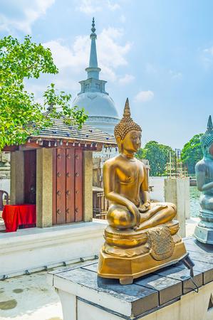 pieris: The white Stupa behind the golden statue of Buddha Touching Earth in Seema Malaka Temple of Gangaramaya Complex, Colombo, Sri Lanka.