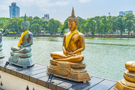 vihara: The row of sitting statues of Lord Buddha on Beira Lake in Seema Malaka Temple, Colombo, Sri Lanka. Stock Photo