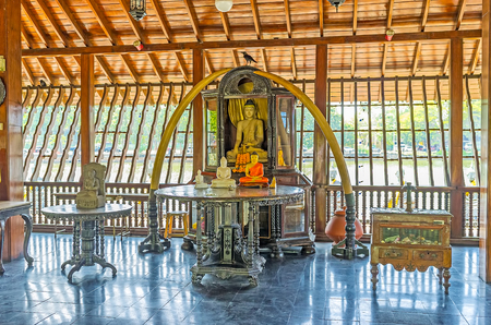 pieris: COLOMBO, SRI LANKA - DECEMBER 7, 2016: The main shrine of Seema Malaka Temple with carved wooden altar of Lord Buddha and big elephants tusks from both sides of it, on December 7 in Colombo. Editorial