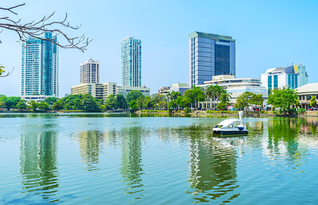 pieris: The swan catamaran in Beira lake with the modern business district on the background, Colombo, Sri Lanka. Stock Photo