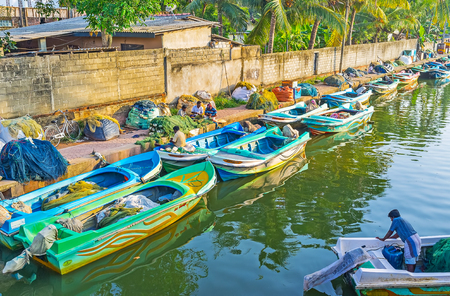 NEGOMBO, SRI LANKA - DECEMBER 7, 2016: Two rows of old boats on Hmiltons Canal in fishing village district, on December 7 in Negombo.