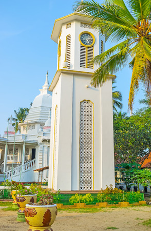 The beautiful clock tower of Angurukaramulla Buddhist Temple (Bodhirajaramaya)  decorated with carved patterns and surrounded by green palms and another temple buildings, Negombo, Sri Lanka.