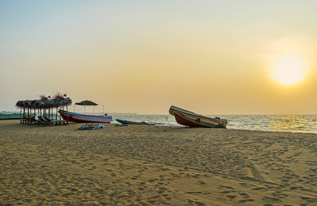 The sunset is the most romantic time for the walks along the cozy sand beach of Negombo with fishing boats, and sunbeds under the sunshades, Sri Lanka.