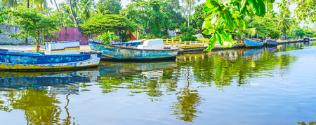 The fishing boats are reflected in waters of Hamiltons Canal, Wattala suburb, Colombo, Sri Lanka. Editorial