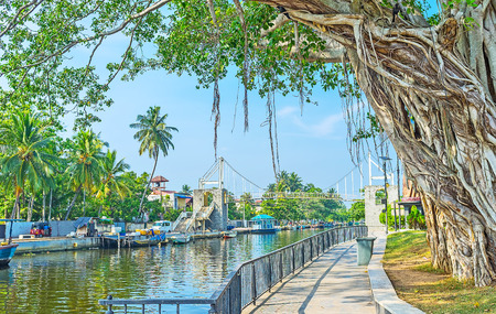 city park boat house: The picturesque park on the bank of Hamiltons Canal with shady green tropical trees, bridges above the canal and cozy embankments, Wattala suburb, Colombo, Sri Lanka. Editorial