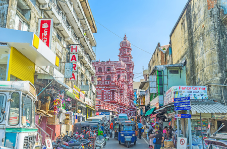 COLOMBO, SRI LANKA - DECEMBER 7, 2016: The towers and domes of Jami-Ul-Alfar Mosque (Red Masjid), located behind the numerous tuk tuks and stalls in narrow street of Pettah market, on December 7 in Colombo.