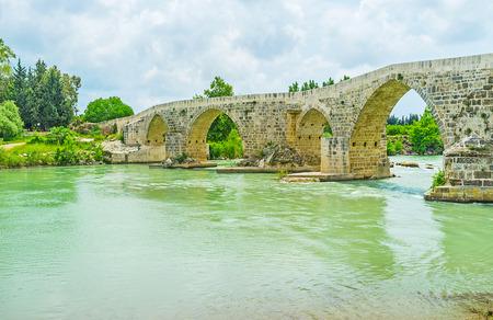 Zigzag Seljuq bridge is the pearl of Eurymedon river, many tourists visit it during the tours to Aspendos, Turkey. Stock Photo
