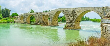 The old Eurymedon bridge is located in the picturesque place, on the same named river and surrounded by green forests and picnic zones, Aspendos, Turkey.
