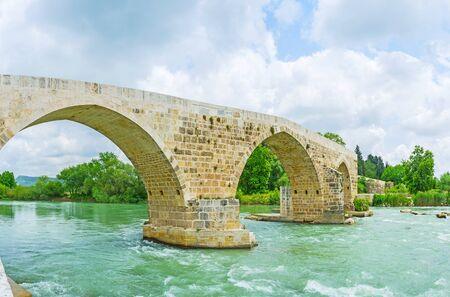 The old arched bridge on Eurymedon river is the notable landmark, located next to Aspendos, Turkey. Stock Photo