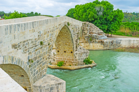 The medieval winding bridge over Eurymedon river was created by Seljuqs on the base of ancient Roman construction, Aspendos, Turkey. Stock Photo