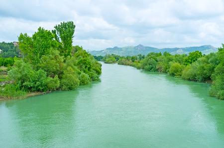 The lush greenery on the banks of fast Eurymedon river, Aspendos, Turkey.