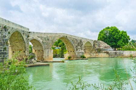 The winding arches of the old Eurymedon Bridge, surrounded by green banks and neighboring with Aspendos archaeological site, Turkey.