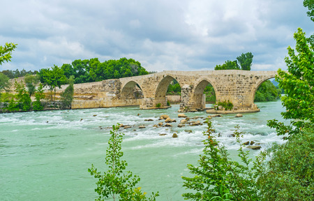 Picnic on the bank of Eurymedon river with a view on the old Seljuq bridge, reconstructed after the Roman era, Aspendos, Turkey.