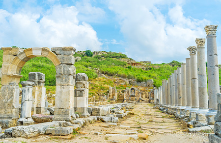 The colonnaded street in Perge decorated with Numphaeum Fountain, Arch of Apollonius and the water canal between these objects, Antalya, Turkey.