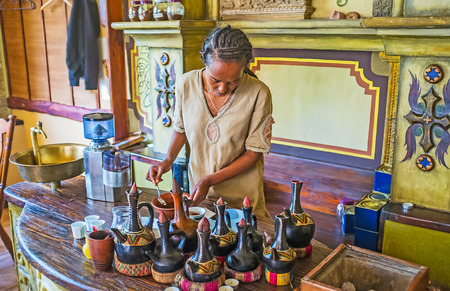 KIEV, UKRAINE - JUNE 4, 2017: Traditional Ethiopian coffee ceremony is always performed by women -young Tigrayan girl brews coffee in traditional way with jebena pot on the charcoal, on June 4 in Kiev.