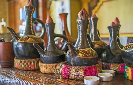 バー アフリカのカフェではコーヒー ・ セレモニーのためのコーヒーを醸造するための鍋を沸騰する多くの伝統的なエチオピア jebena のカウンター。
