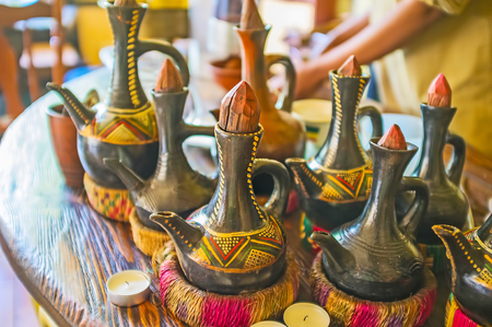 Traditional Ethiopian pottery jebena boiling pots for the ethnic coffee ceremony are decorated with colored patterns, has handmade wooden lids and the stands under the hot, made of grass rope. Zdjęcie Seryjne