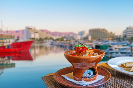 The dinner in restaurant of marina on sunset - the Eastern style beef in a dish with burner, Eilat, Israel. Stock Photo