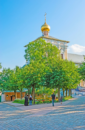 SERGIYEV POSAD, RUSSIA - JUNE 29, 2013: The golden dome of Refectory Church of St Sergius Trinity Lavra rises over the lush greenery of local garden, on June 29 in Sergiyev Posad. Editorial