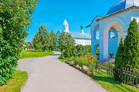 The way along the green garden of Suzdal Intercession Monastery with a view on the belfry of Refectory and Conseption church on the distance, Russia.
