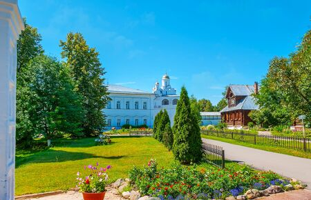 The scenic flower beds, juicy green lawn and lush trees decorate the garden of Suzdal Intercession Monastery, the Annunciation Gate Church is seen on the background, Russia.