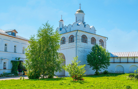 The Main Gateway of Intercession Monastery is topped with Annunciation church and surrounded by garden, Suzdal, Russia. Stock Photo