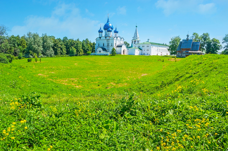 The green meadow is surrounded by old shafts of Suzdal Kremlin, nowadays serving as the viewpoints for tourists, enjoying the medieval architecture from here, Russia.