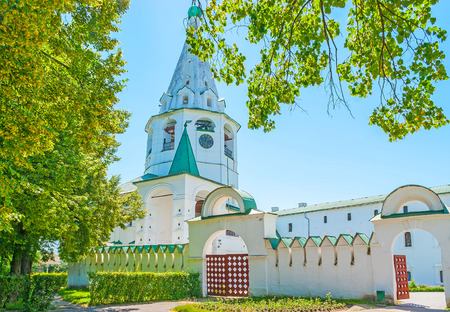 The medieval wall and gates of Suzdal Kremlin, the Cathedral bell tower with clock is seen on background, Russia.