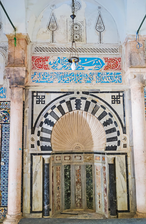 The carved stone mihrab in Mosque of Bir Lahjar Madrasa, decorated with Islamic patterns and calligraphic Arabic inscriptions