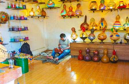 lamp shade: ANTALYA, TURKEY - MAY 12, 2017: The craftsman at the workshop makes the shade of dry pumpkin, decorated by unique patterns, Old Bazaar, on May 12 in Antalya.