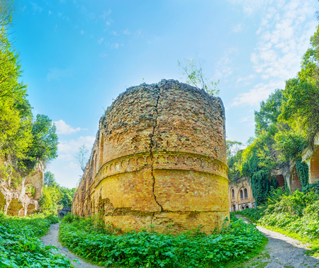The view on inner buildings of ruined Tarakanov Fort, surrounded by lush greenery, Dubno, Ukraine