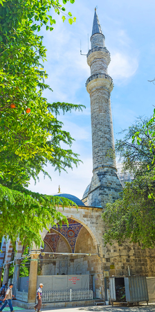 ANTALYA, TURKEY - MAY 12, 2017: The  tall stone minaret and huge porch of Muratpasa Mosque in old town, on May 12 in Antalya.