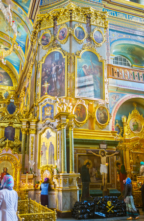 POCHAYIV, UKRAINE - AUGUST 30, 2017: Interior of Holy Dormition Cathedral of Pochayev Lavra decorated with gilded icons that depict stories from the Holy Bible, on August 30 in Pochayiv.