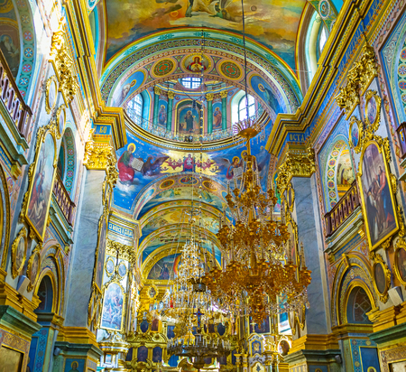 POCHAYIV, UKRAINE - AUGUST 30, 2017: Interior of Holy Dormition Cathedral with arched ceiling decorated with frescoes and icons on the walls, on August 30 in Pochayiv. Editorial