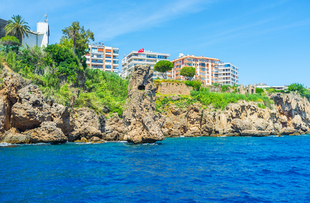 city park boat house: Antalya boasts scenic coastline with tall cliffs, rocks in sea, lush green gardens and modern building on the top, Turkey. Stock Photo
